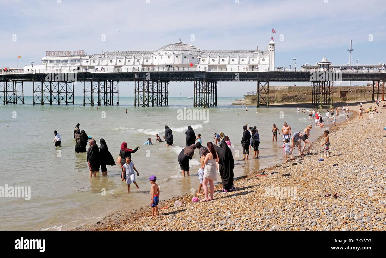 Brighton, UK. 24th Aug, 2016. Crowds including Muslim families flock to Brighton beach to enjoy the hot sunshine - Stock Image