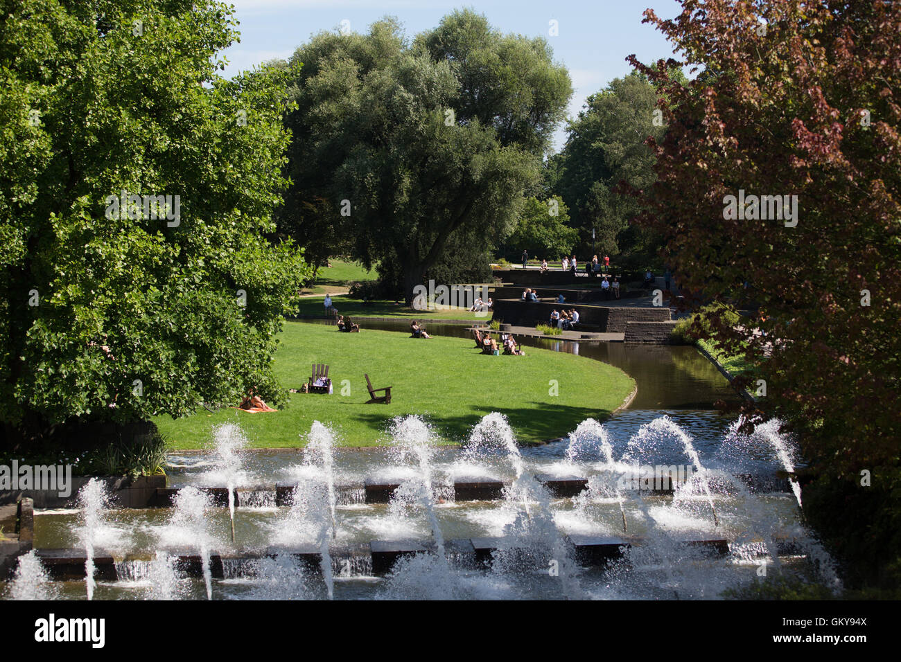 Hamburg, Germany. 24th Aug, 2016. People enjoying the sun next to a fountain in the park 'Planten un Blomen' - Stock Image