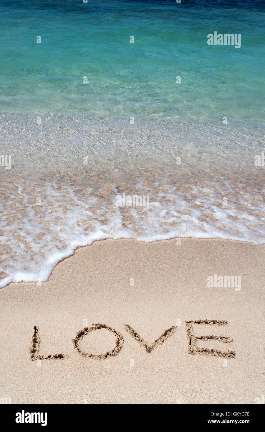 Romantic beach getaway with the word Love handwritten in the golden beach sand - Stock Image