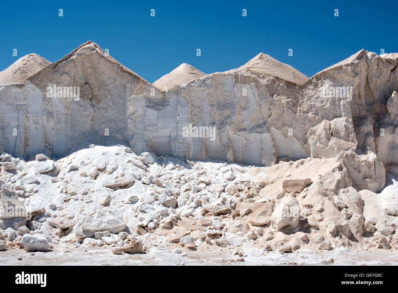 Mounds of salt or saline dried out by evaporation of the hot sun at a commercial salt farm under a clear sunny blue - Stock Image