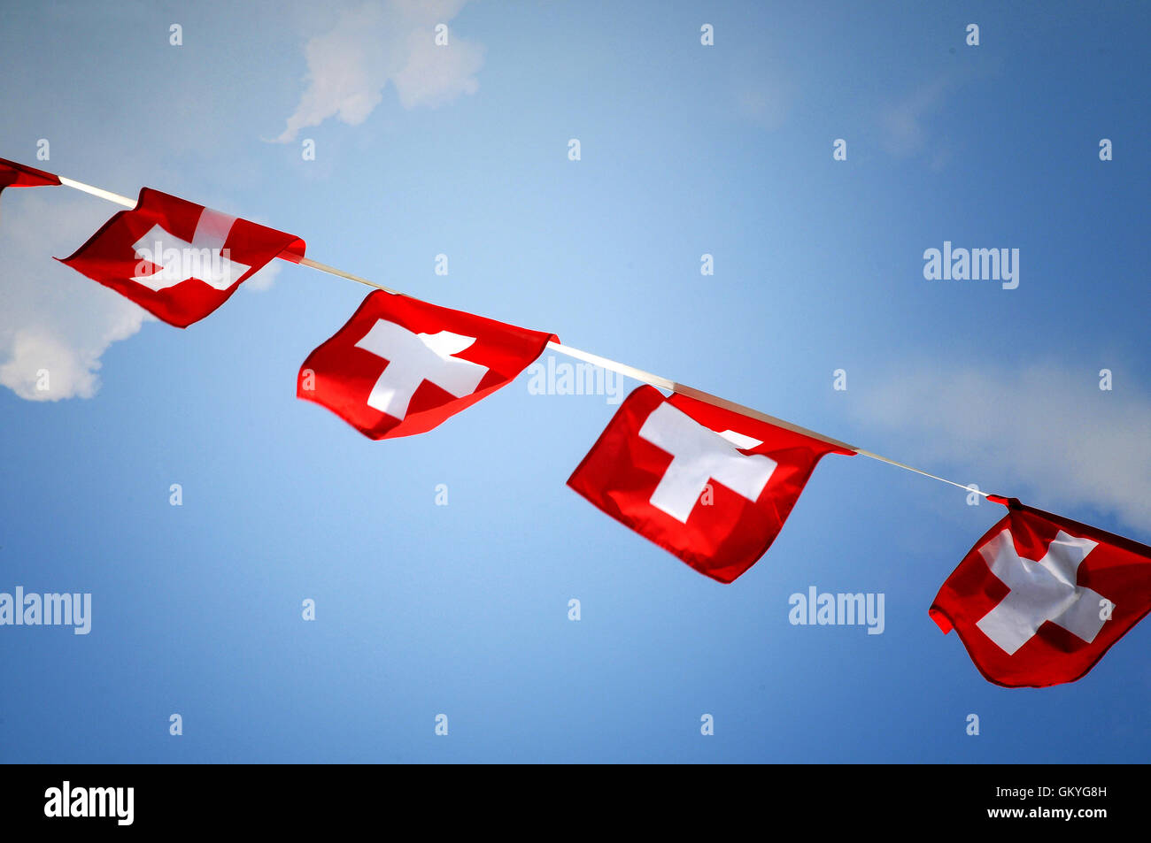 Row of colorful red bunting with the Swiss national flag flying in the breeze - Stock Image