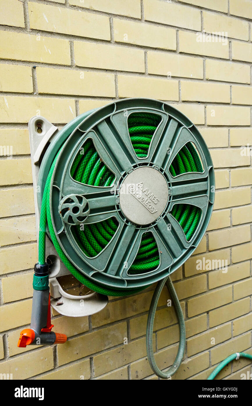 A garden hosepipe coiled up reel system on a brick house wall - Stock Image