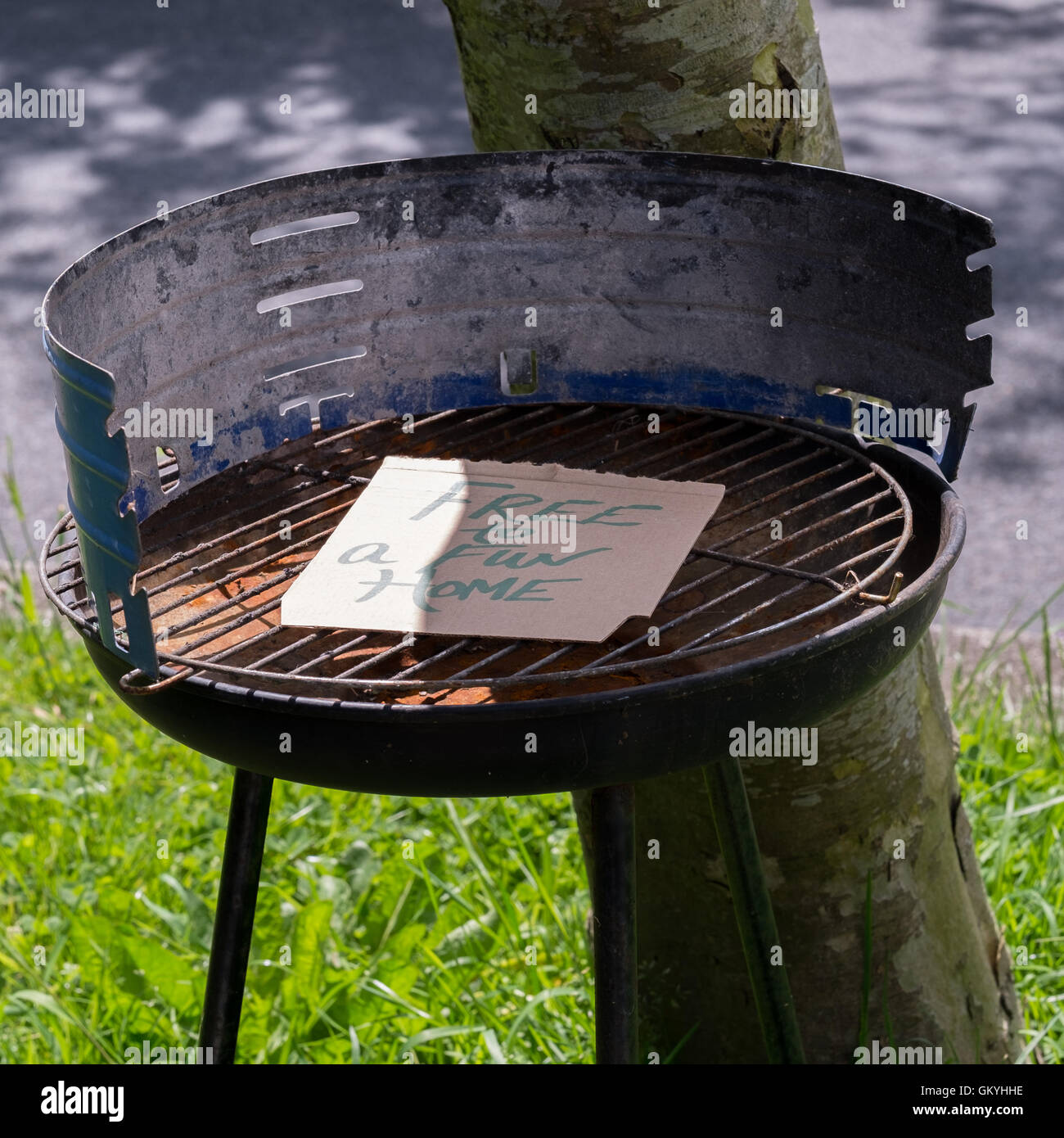 A barbeque being freecycled by the side of the road with a message reading 'Free to a fun home'. - Stock Image