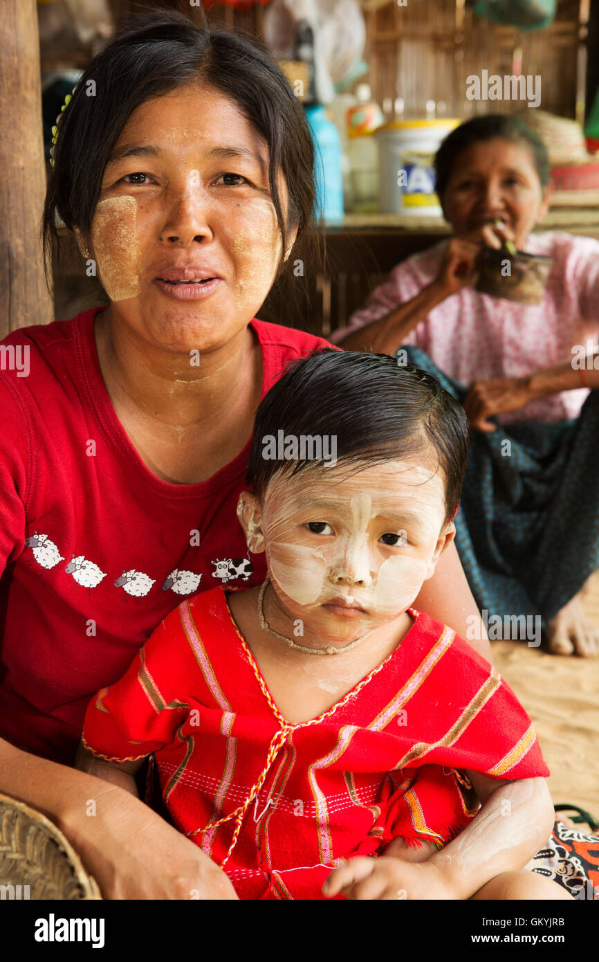 A Burmese woman and child at a house in Minnathu Village near Bagan, Myanmar (Burma). Both wear face paint known - Stock Image