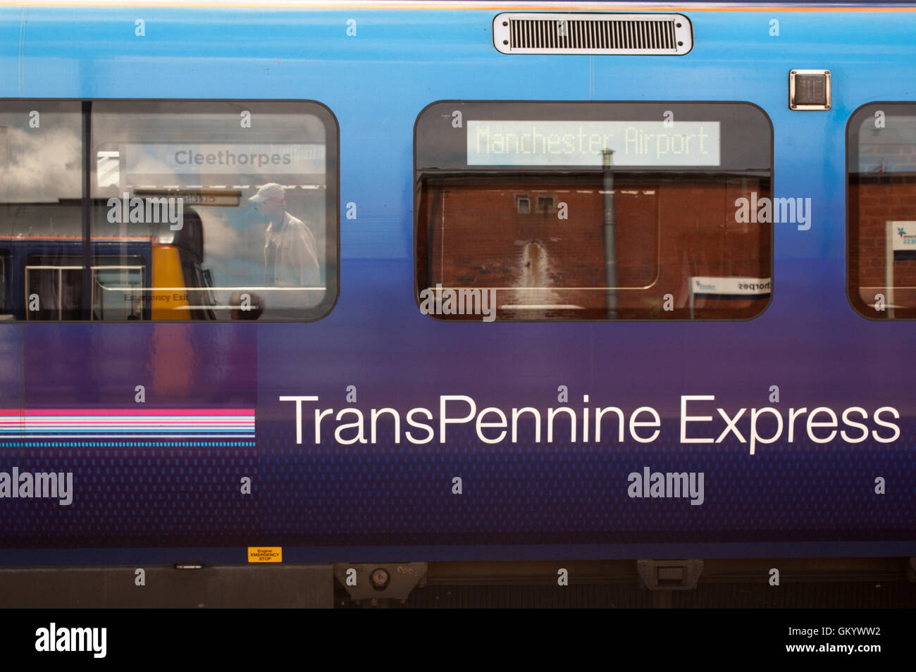 TransPennine Express train at Cleethorpes station with reflection of Northern Rail Pacer unit - Stock Image