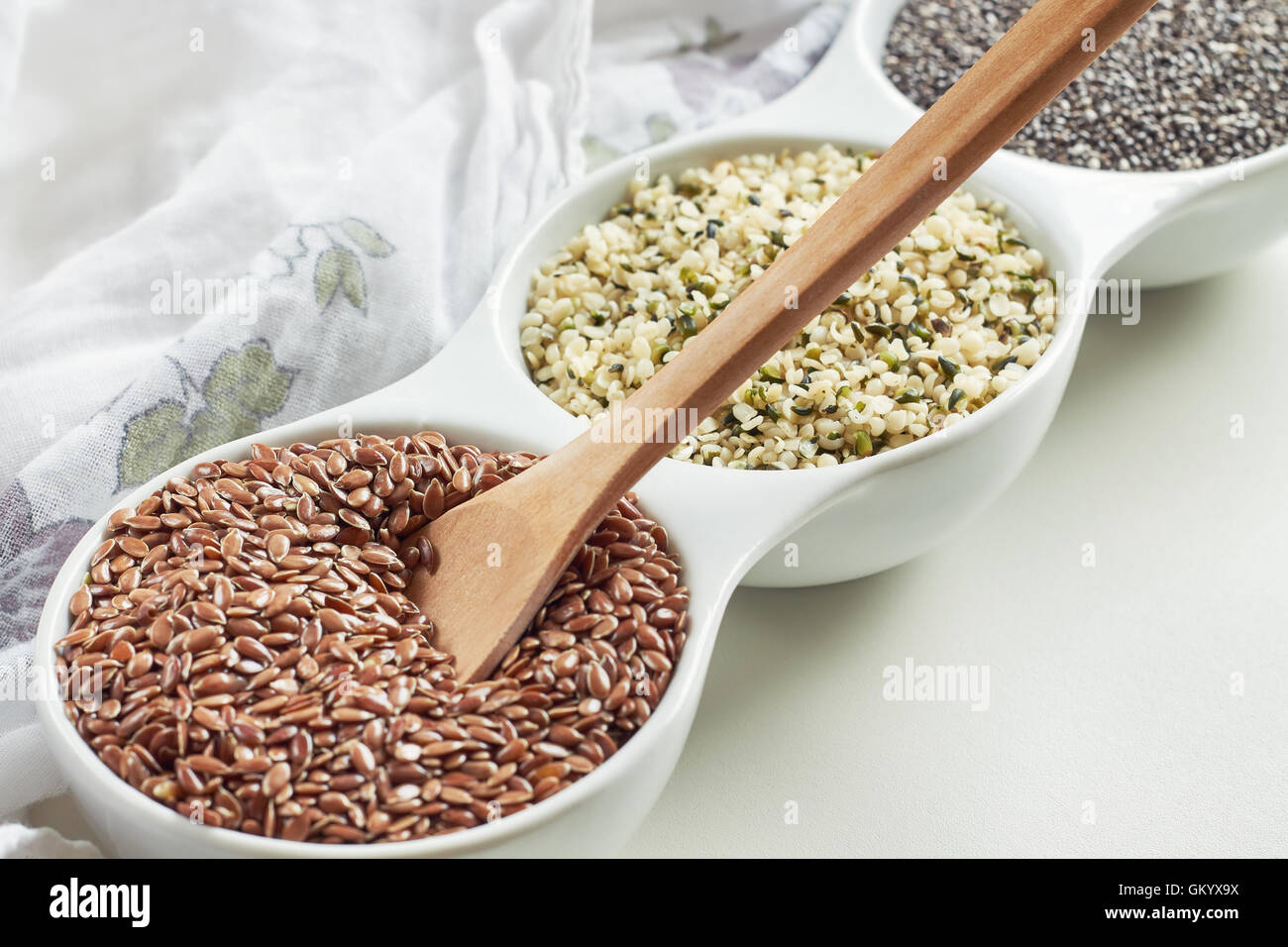 Flax, hemp and chia seeds in bowl on white background. Vegan sources of Omega-3 - Stock Image