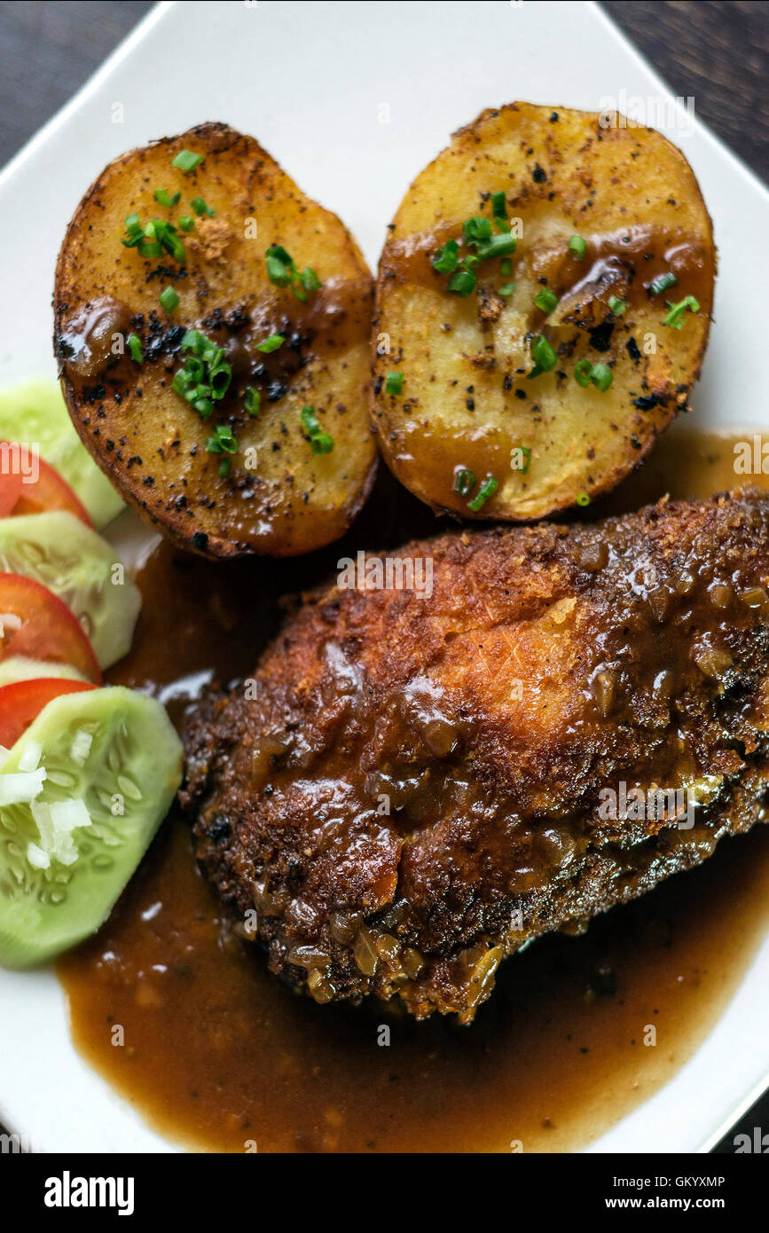 famous cordon bleu breaded fried chicken gravy and potatoes meal - Stock Image