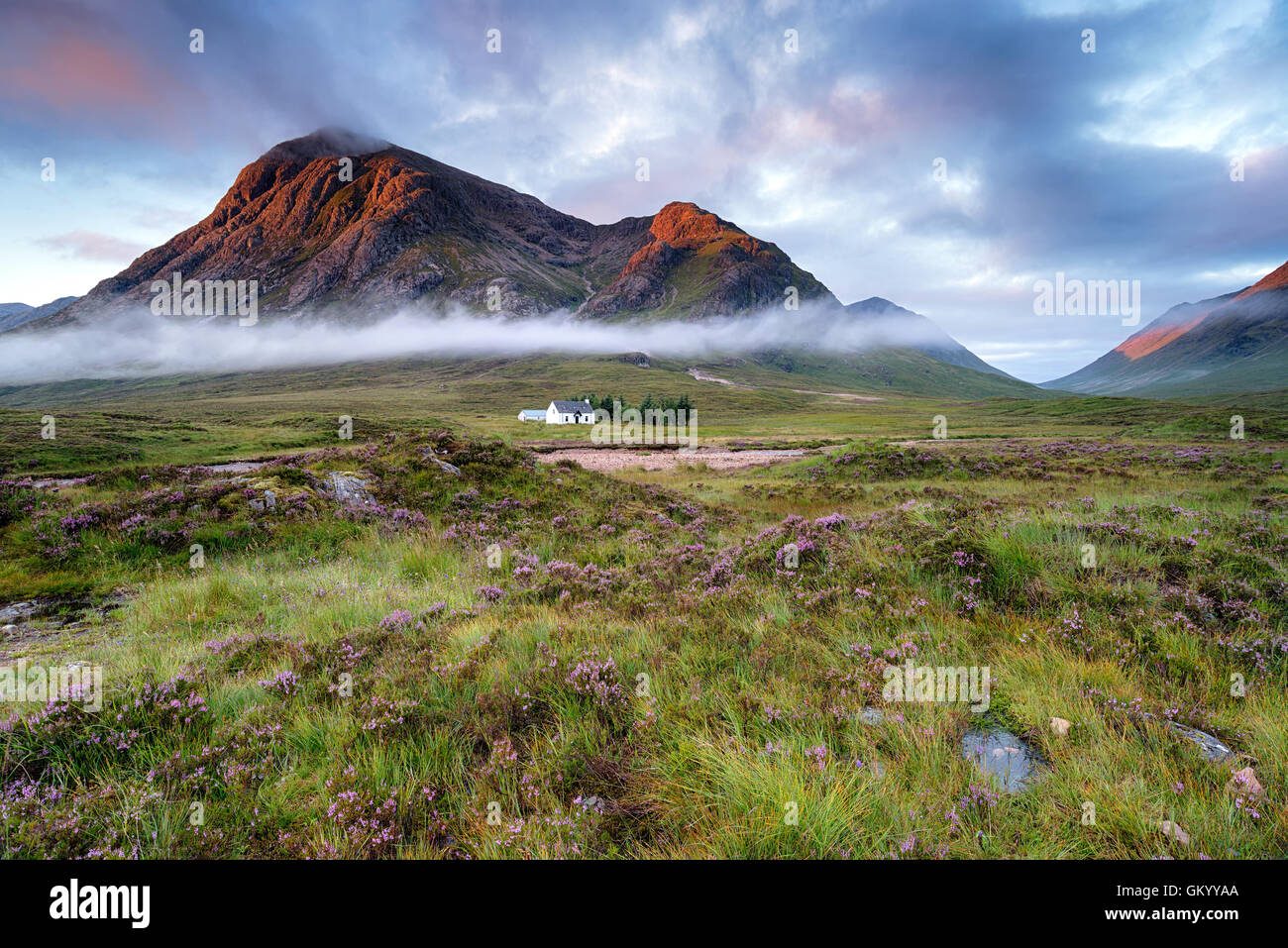 Stunning sunrise over a cottage beneath the mountains at Glencoe in the Scottish Highlands - Stock Image