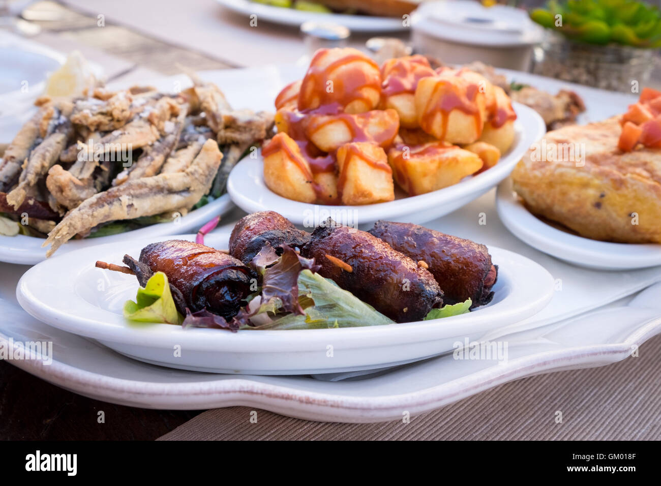 A selection of Mallorcan Tapas dishes, including dates wrapped in bacon pictured front - Stock Image