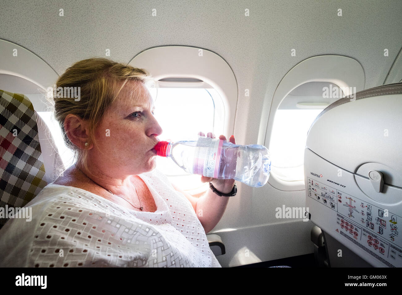 A woman drinking a bottle of water to stay hydrated during a flight on a plane - Stock Image