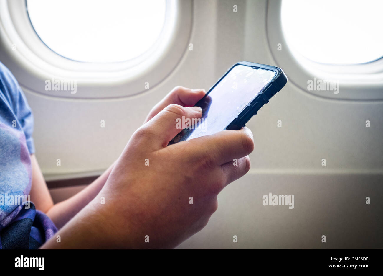 A teenage boy using his mobile phone during the flight on a plane - Stock Image