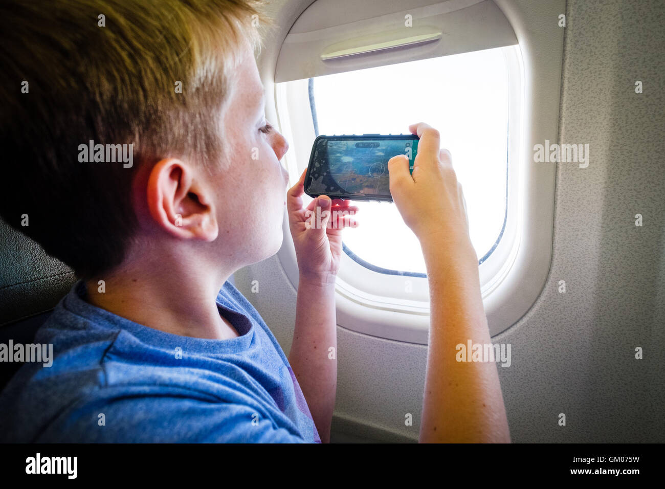 A teenage boy using his mobile phone during the flight on a plane to take a photo out of the window - Stock Image