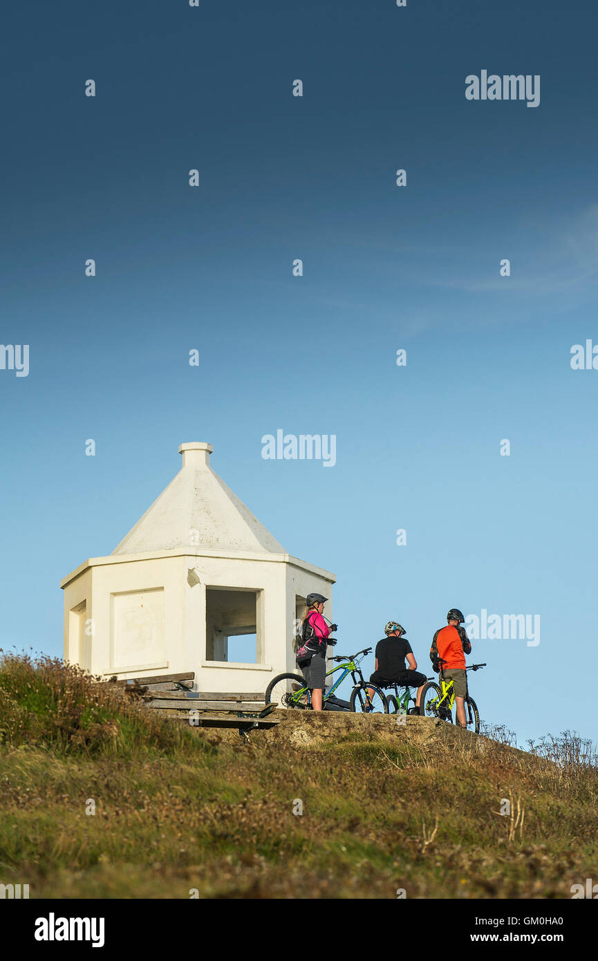 Three mountain bikers stand next to the white lookout building on top of Towan Headland in Newquay, Cornwall. - Stock Image