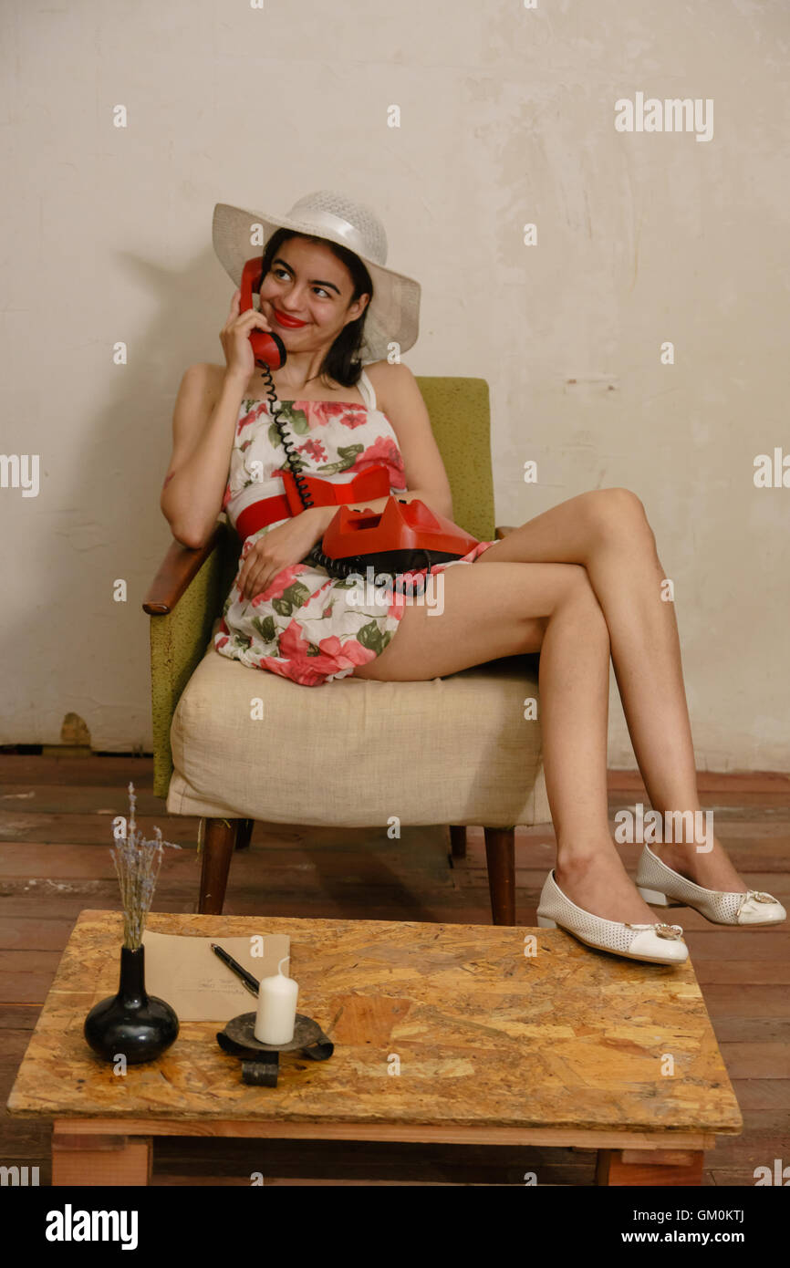 girl with long lovely legs calls to someone by retro red phone sitting on the old arm-chair in white hat and prettily - Stock Image