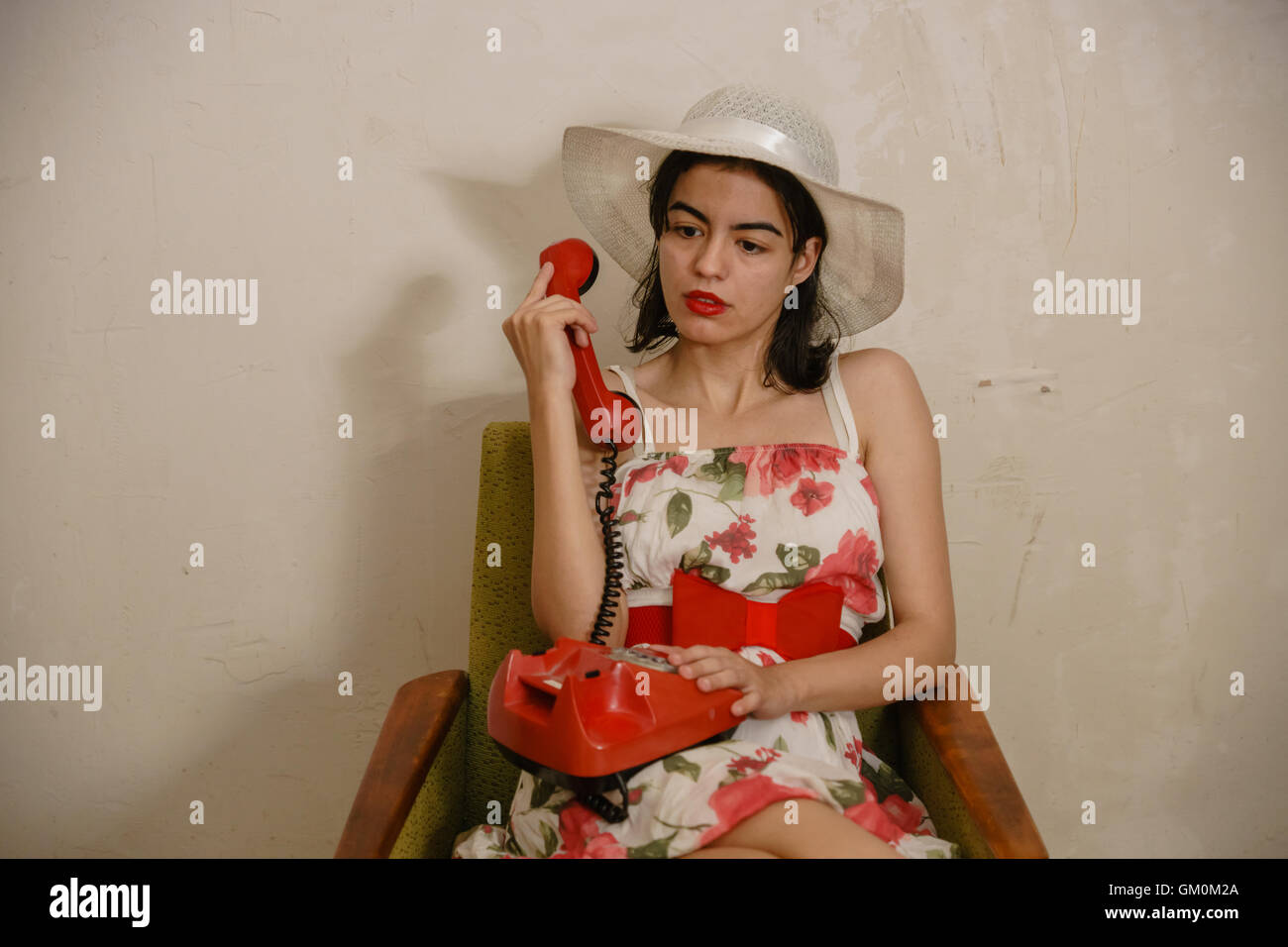 e9ecd33d pretty girl in white hat put retro phone on the her knees and wistfully  looks somewhere