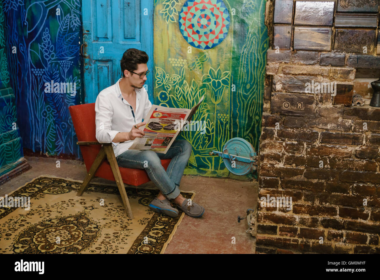 thoughtful reading of young man on the old armchair. There are old stove with opened flap near to reading man - Stock Image