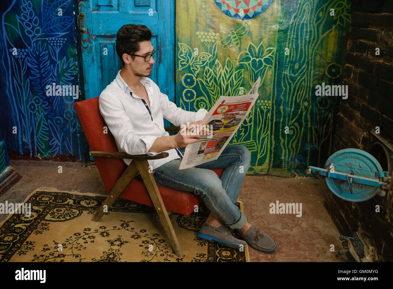 thoughtful reading of young man on the old armchair beside unusual wall. There are old stove near to reading man Stock Photo