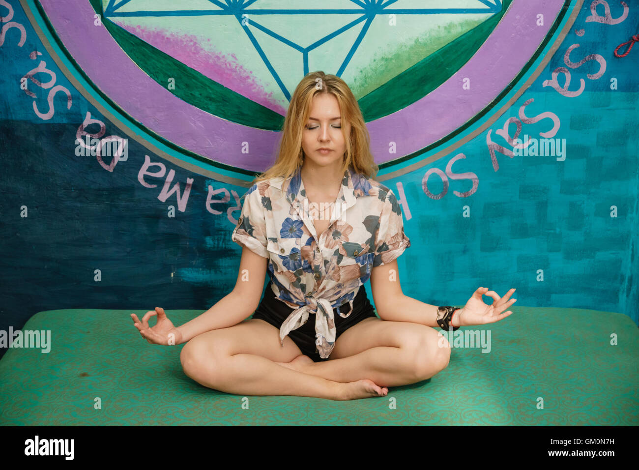 pretty woman meditates on the sofa in pose of lotus with closed eyes - Stock Image