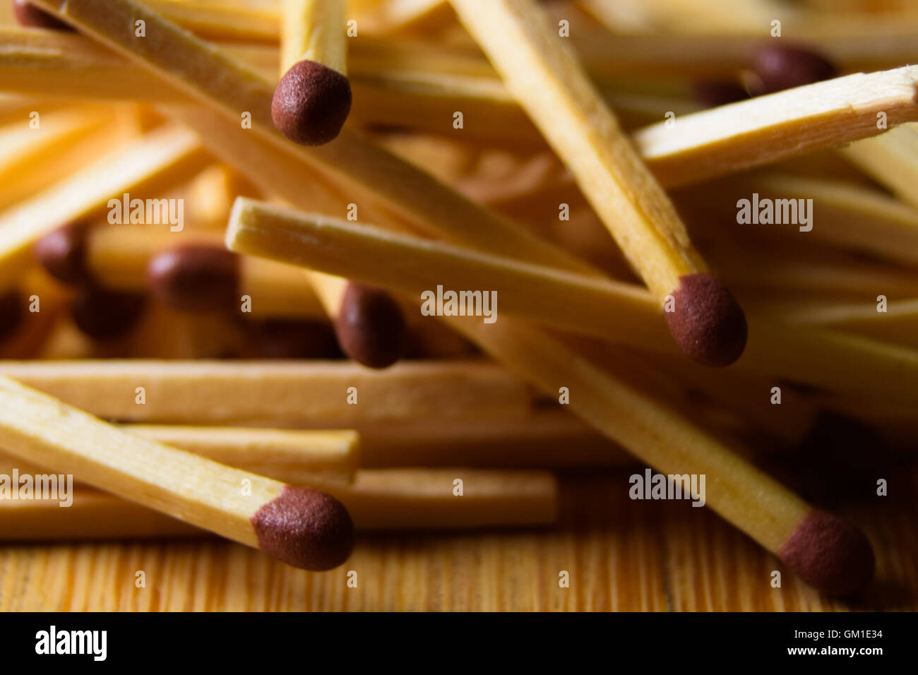 Pile of matches in a random bundle on a wooden table, close up - Stock Image