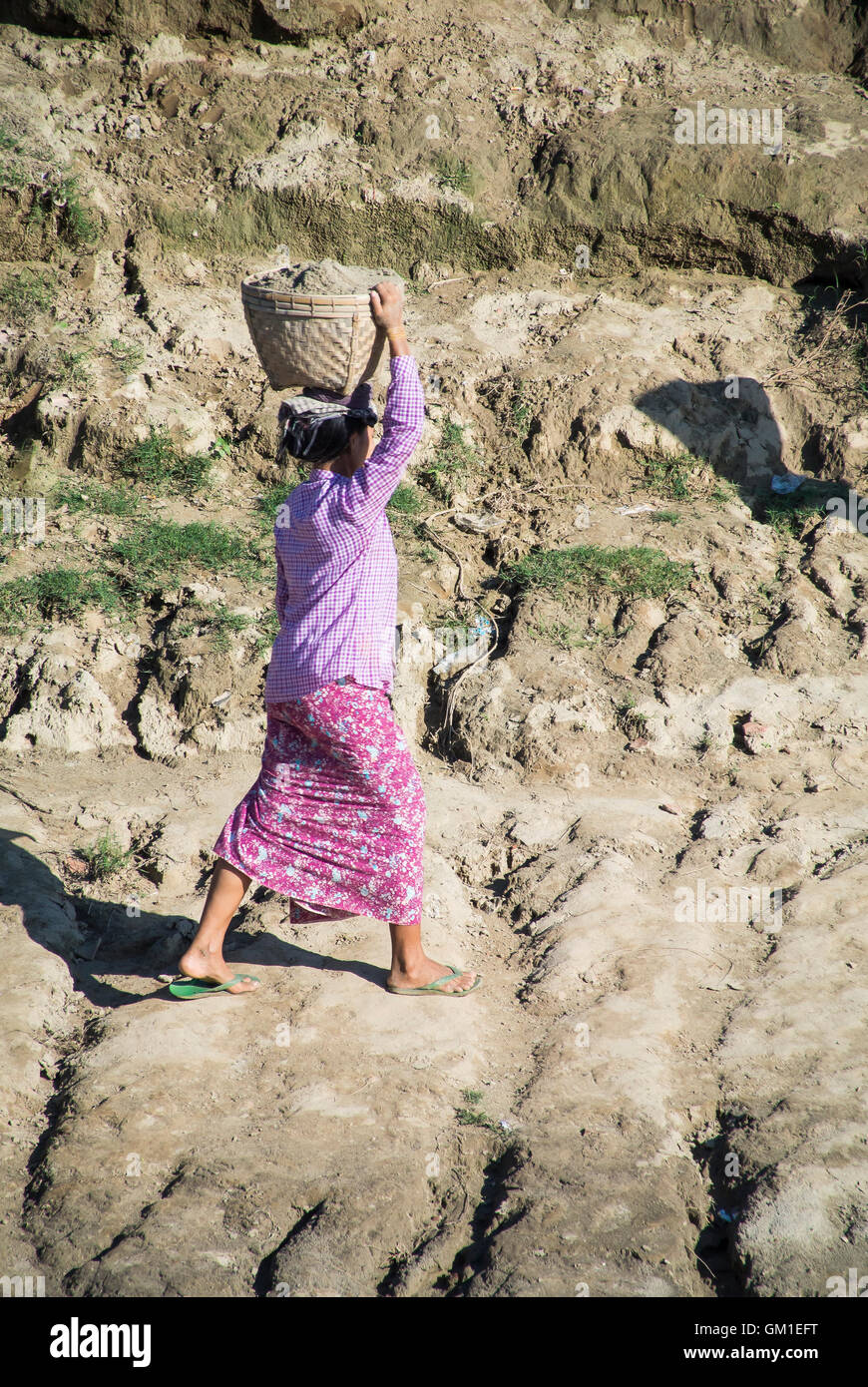Village Woman Carrying Clay From River's Edge to Top of Bank, Myanmar - Stock Image