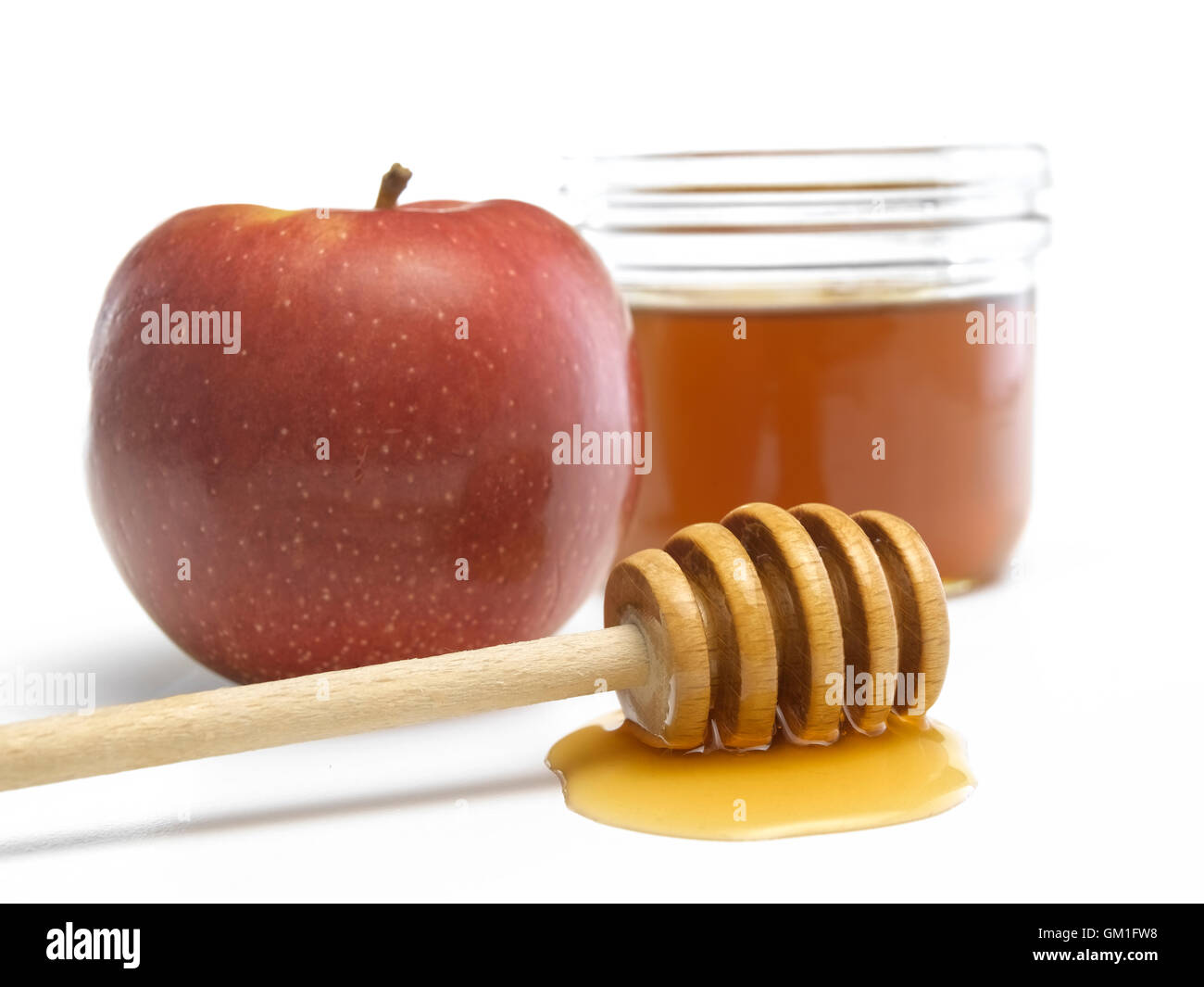 Runny honey with a wooden dipper and a red apple - Stock Image