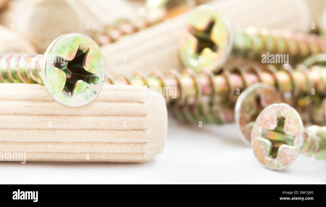 Close up of screws and wooden peg fasteners background - Stock Image