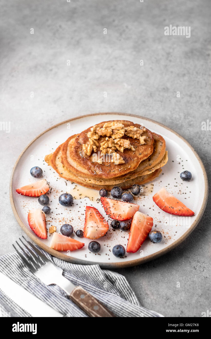 Fresh blueberry pancakes with honey, strawberries, blueberries, walnuts and chia seeds - Stock Image
