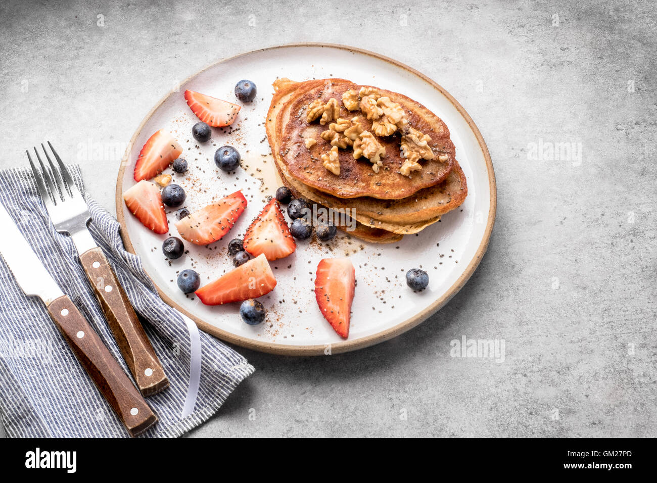 Fresh blueberry pancakes with honey, strawberries, blueberries, walnuts and chia seeds Stock Photo