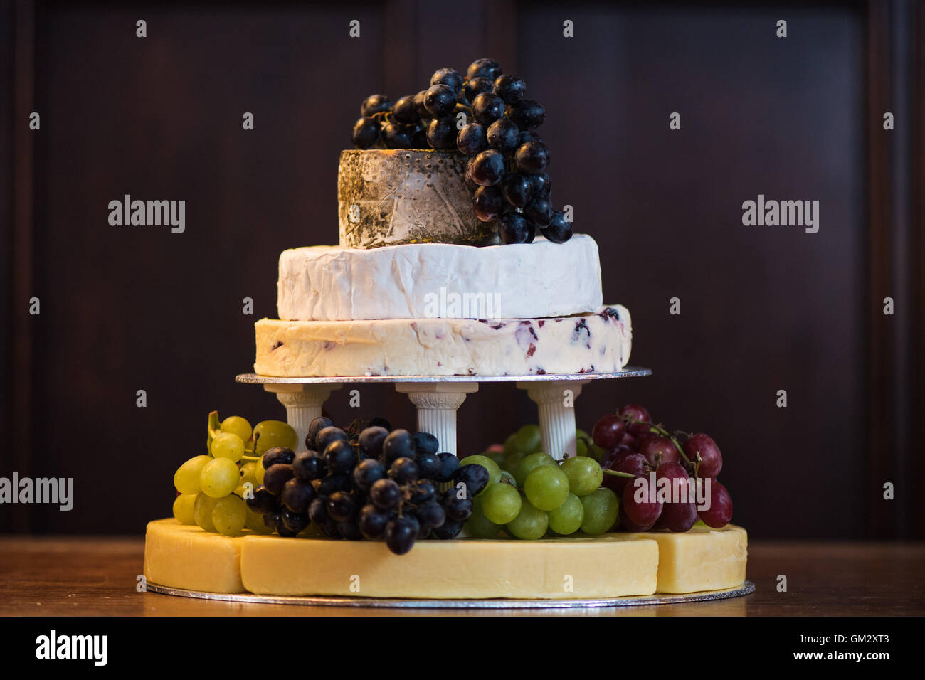A stack of cheeses with grapes forming a cake at a wedding reception - Stock Image