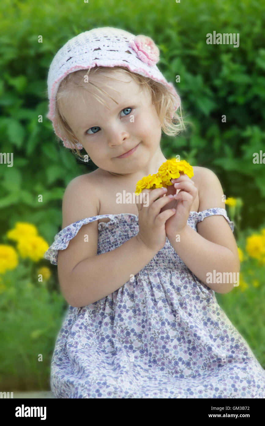 Coquettish little girl portrait with flowers - Stock Image