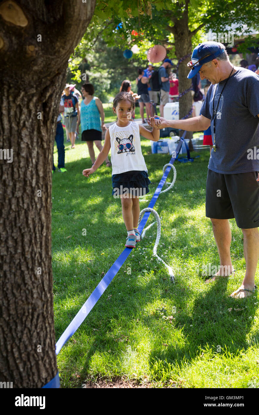Wheat Ridge, Colorado - A girl walks on a slackline during a July 4 parade and picnic in suburban Denver. - Stock Image
