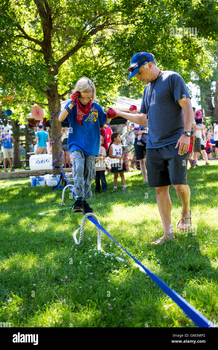 Wheat Ridge, Colorado - A child walks on a slackline during a July 4 parade and picnic in suburban Denver. - Stock Image