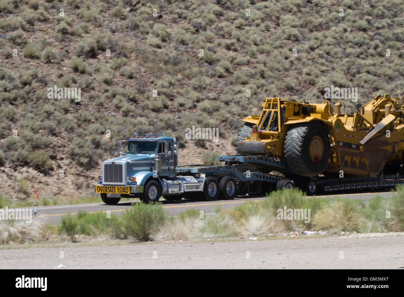 Large truck hauling an earth moving machine. USA - Stock Image