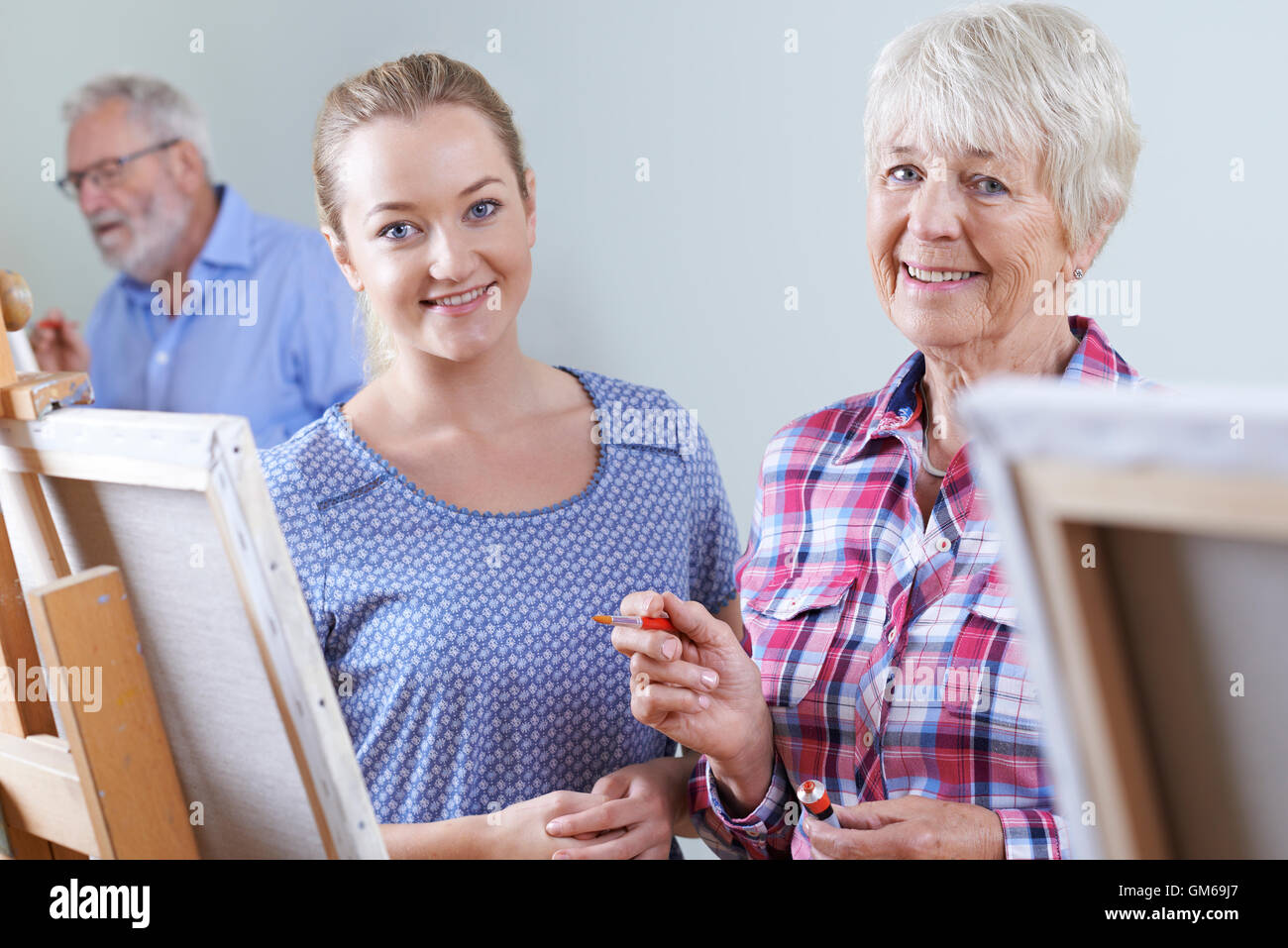 Seniors Attending Painting Class With Teacher - Stock Image