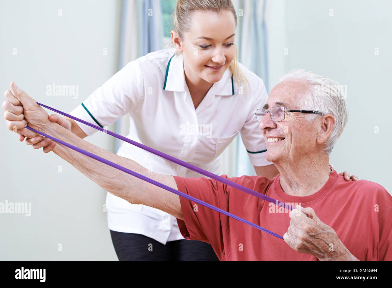 Physiotherapist Helping Senior Male To Use Resistance Band - Stock Image