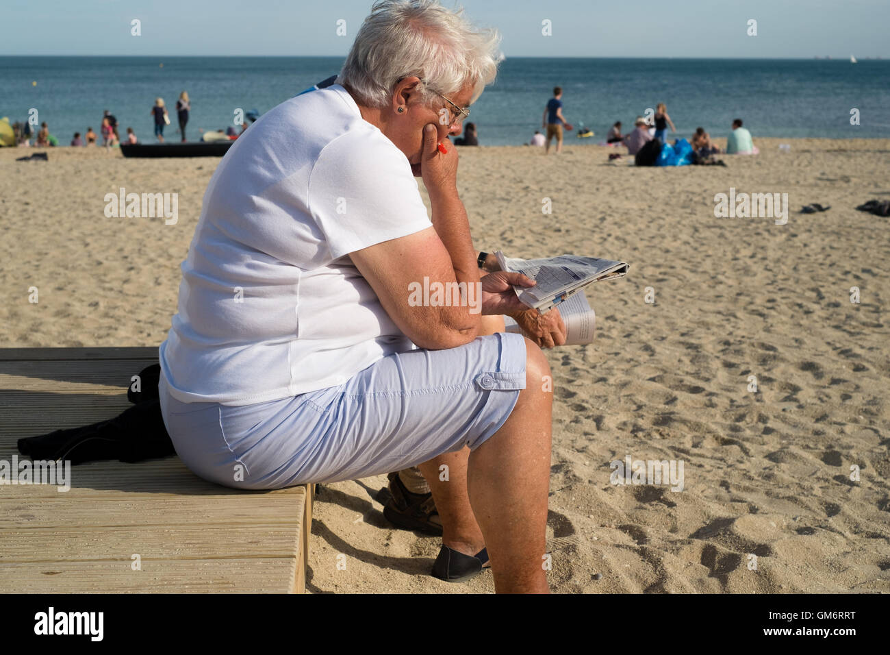 Woman reading the newspaper in the late afternoon sunshine at Gyllyngvase Beach, Falmouth, Cornwall. 24th August - Stock Image