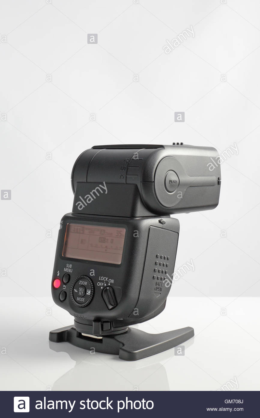 Canon 430EX III-RT Speedlite, powered on and sitting on a reflective surface. - Stock Image