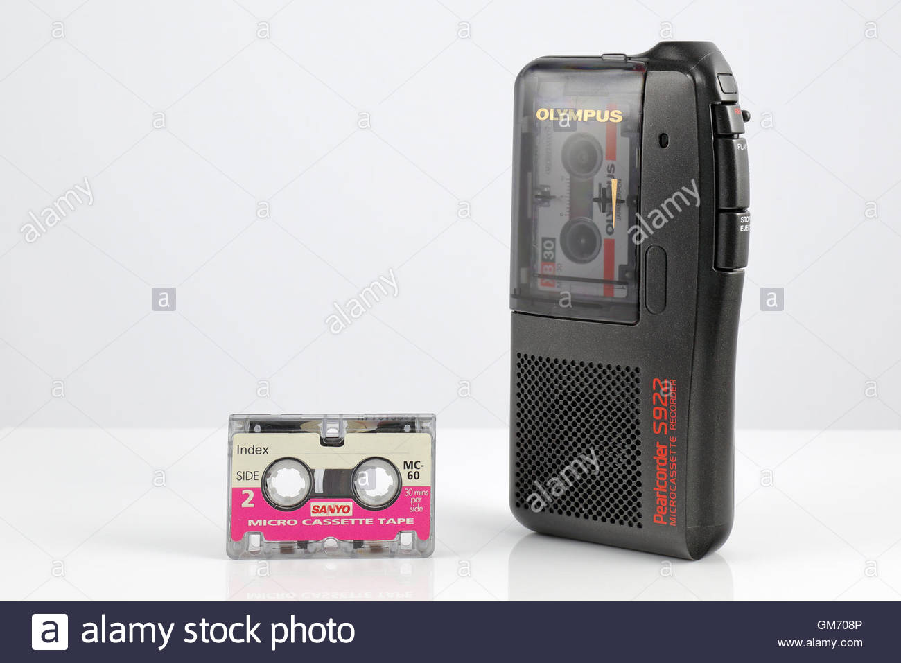 Olympus Pearlcorder S922 Microcassette Recorder and Sanyo Microcassette, placed on a white reflective surface - Stock Image