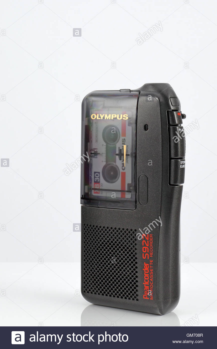 Olympus Pearlcorder S922 Microcassette Recorder placed on a white reflective surface. - Stock Image