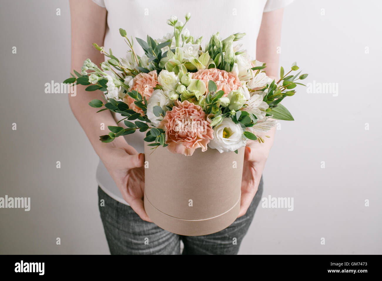 Work florist bouquet in a round box smelling flowers holding peach work florist bouquet in a round box smelling flowers holding peach roses bouquet in hat box against the plastered wall izmirmasajfo