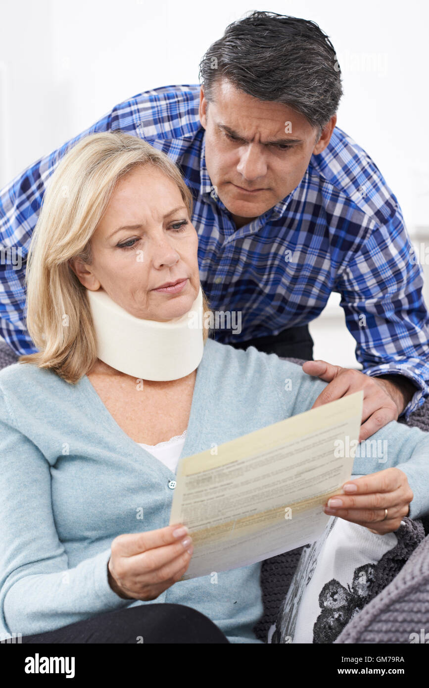 Couple Reading Letter About Wife's Injury - Stock Image