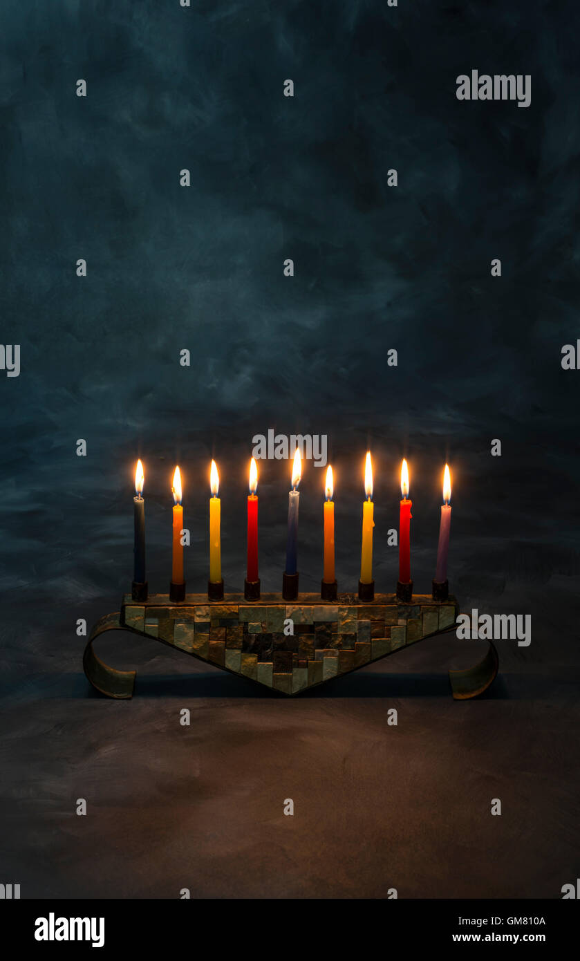 Menorah with burning candles for Hanukkah in dark - Stock Image
