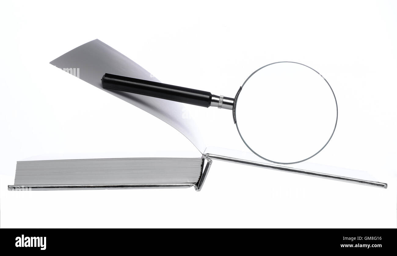 Magnifying Glass on open book - Stock Image