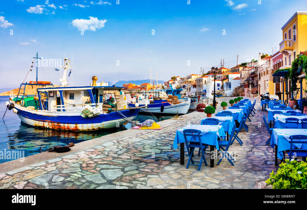 traditional Greece- Chalki island with tavernas and fishing boats - Stock Image