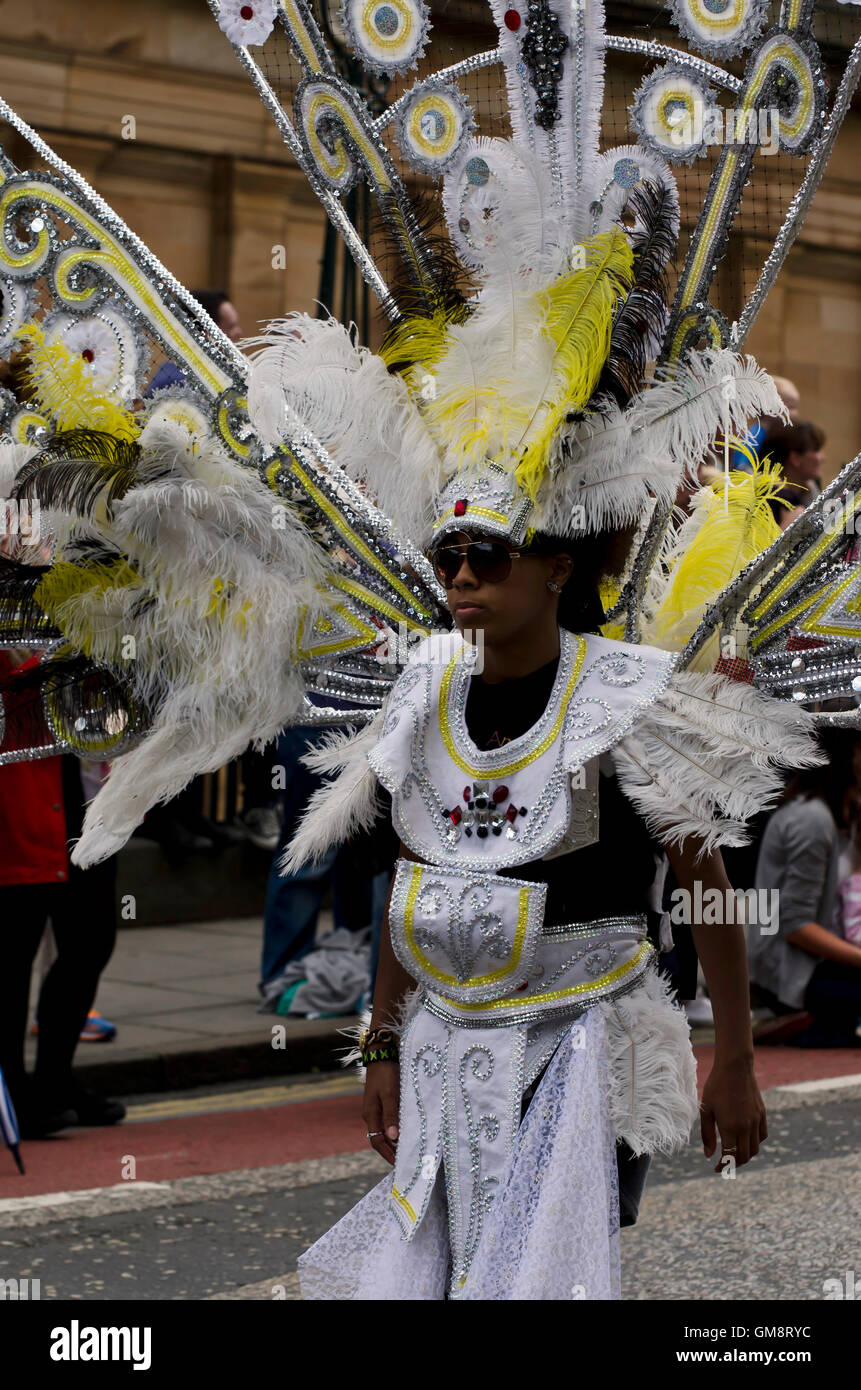 Black man in ornate feathered costume and headdress taking part in the Cavalcade, part of the Edinburgh Jazz Festival. - Stock Image