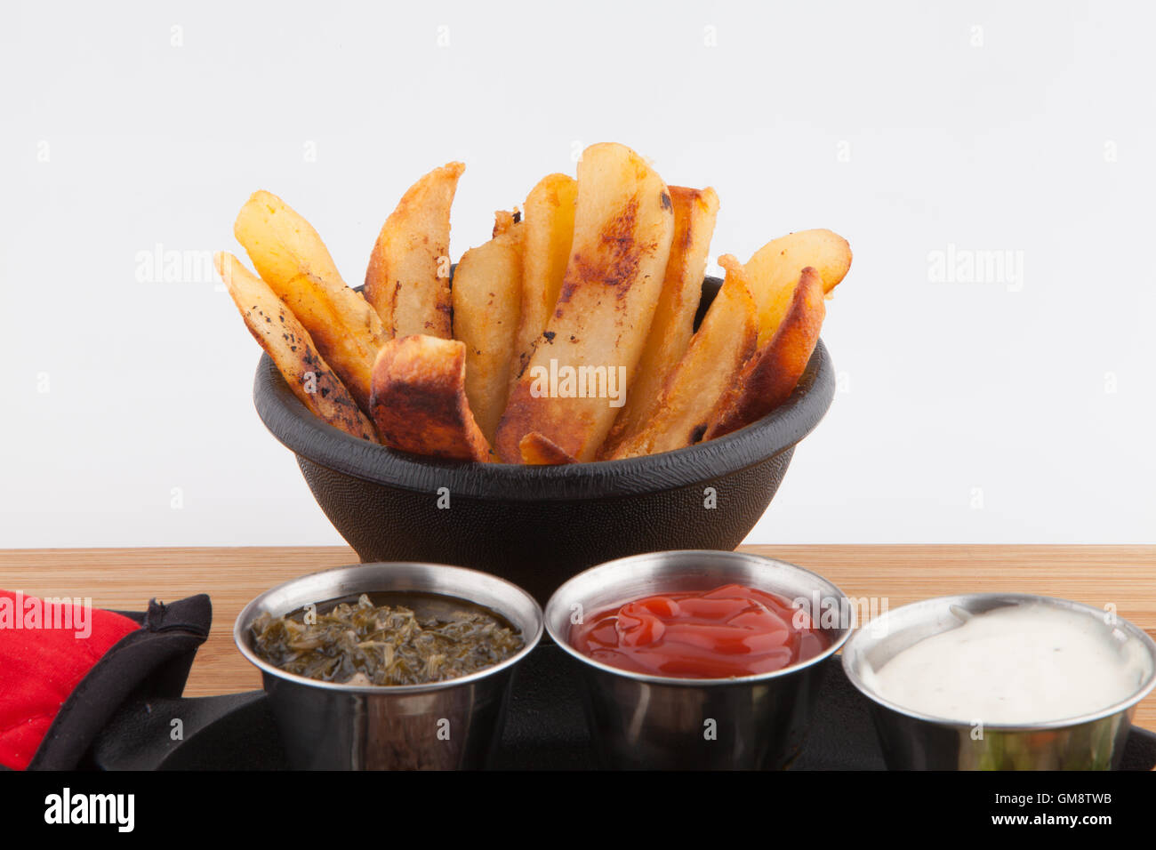 French Fries  garnish sauces Ketchup catsup table sauce Ranch dressing, Chimichurri on a cast iron Stock Photo