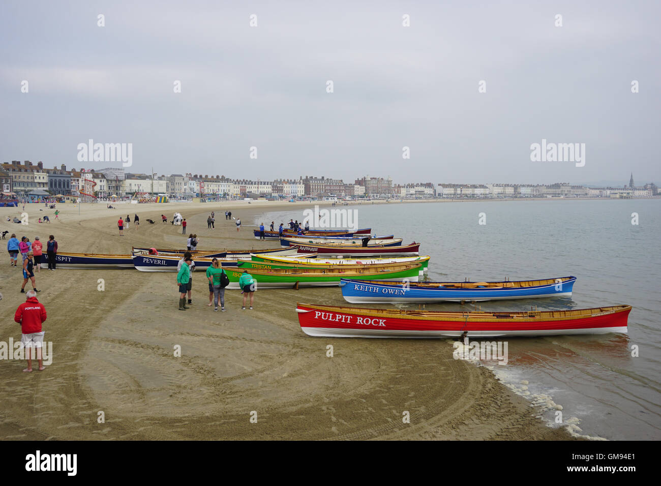 Rowing Gigs on Weymouth beach for a gig race. - Stock Image