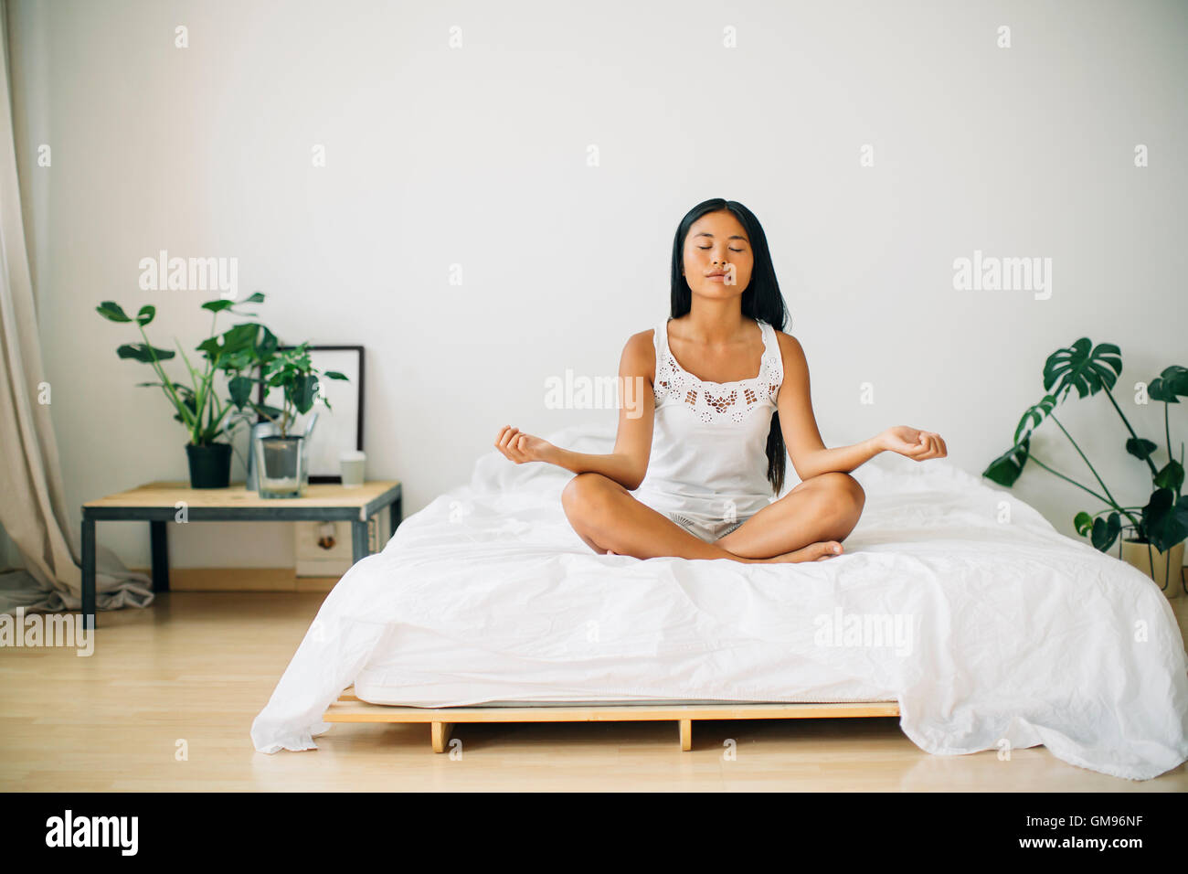 Young woman practicing yoga on bed Stock Photo