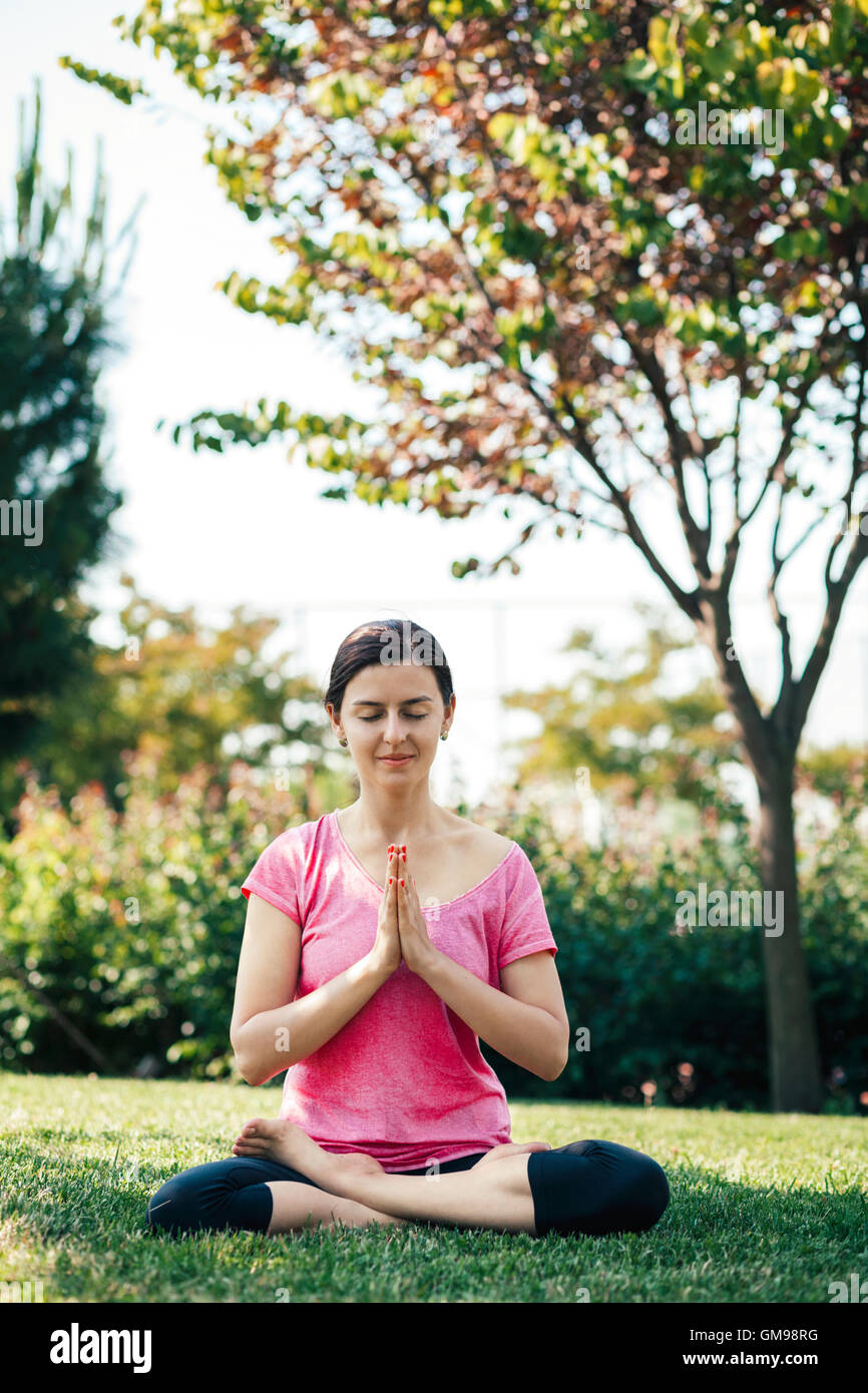 Young woman doing yoga and meditation, outside, eyes closed Stock Photo