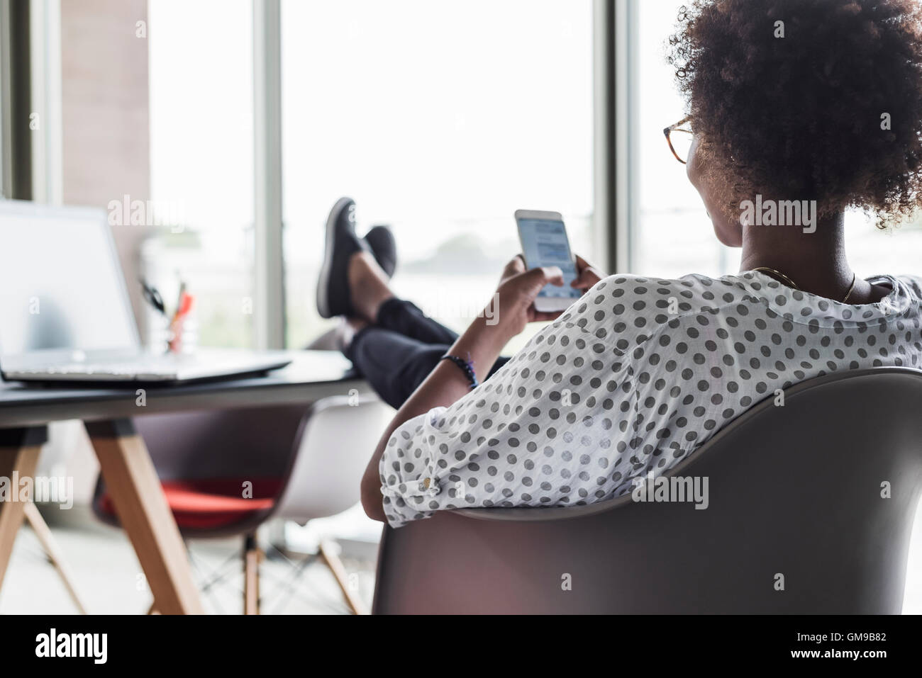Back view of woman text messaging - Stock Image